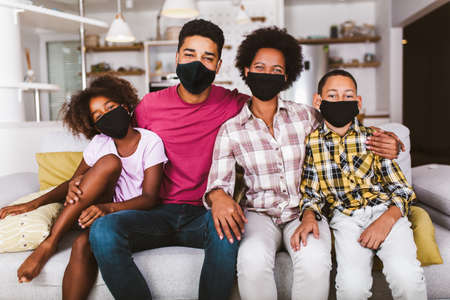 Foto de African American parents and cute small kids wearing protective masks at home. Stop the virus and epidemic diseases. - Imagen libre de derechos