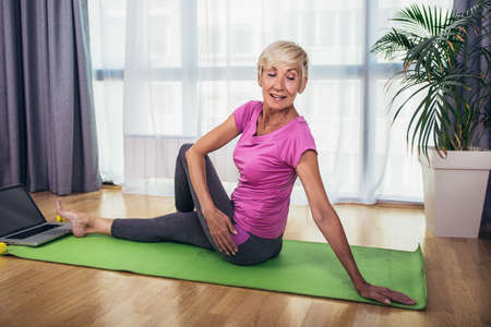 Photo pour Happy senior woman doing stretching exercises in front of laptop at home, watching online tutorials - image libre de droit