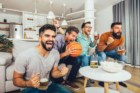 Photo for Happy friends or basketball fans watching basketball game on tv and celebrating victory at home. - Royalty Free Image