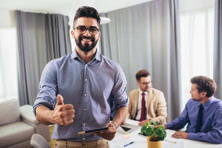 Foto de Leader ceo or professional business coach looking at camera posing in office with diverse happy team at background. - Imagen libre de derechos
