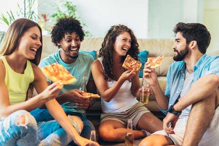 Photo pour Group of young friends eating pizza.Home party. - image libre de droit