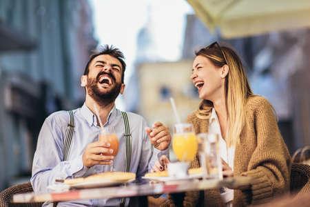 Photo pour Young couple sitting in a restaurant eating pizza - image libre de droit