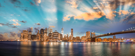 Dramatic sky over Brooklyn Bridge and Manhattan, panoramic night view of New York City