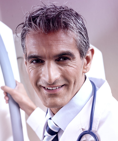 Healthcare, advertisement, people and medicine concept - smiling male doctor in white coat in hospital.