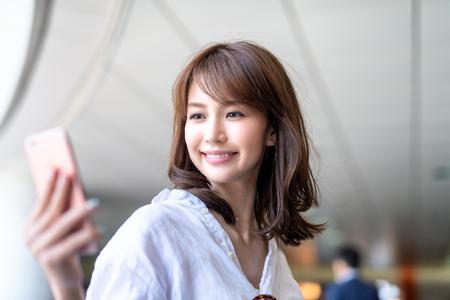 Beautiful japanese woman looking at smartphone inside subway station.