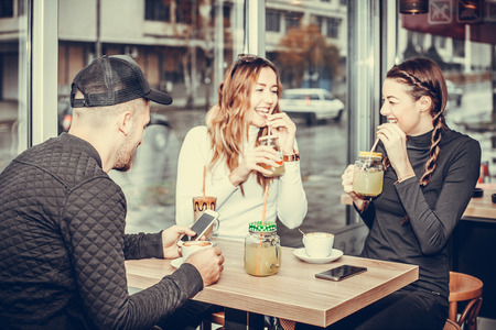 Cheerful group of friends, one man and two women sitting at the table in the cafe shop, talking and having fun laughing smiling happy. Girls drinking lemonade