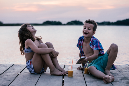 Photo for Portrait of positive children playing with smartphone together on wooden pier. Kids laughing, enjoying the beautiful sunset - Royalty Free Image