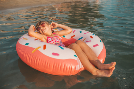 Foto de Happy little girl lying with inflatable ring in water on hot summer day. Kids learn to swim. Child water toys - Imagen libre de derechos