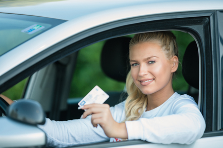 Photo pour Driving school. Attractive young woman proudly showing her drivers license and smiling in vehicle. Free space for text. Copy space. - image libre de droit