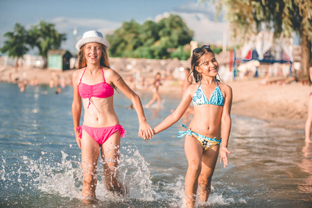 Photo pour Happy little girls running through the water at the beach - Image - image libre de droit