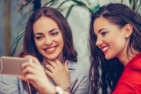 Photo pour Two young women sitting in a cafe looking at mobile phone and smiling. - image libre de droit