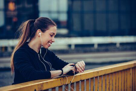 Foto de Young beautiful woman checking fitness progress on her smart watch. Female runner using fitness app to monitor workout performance - Imagen libre de derechos