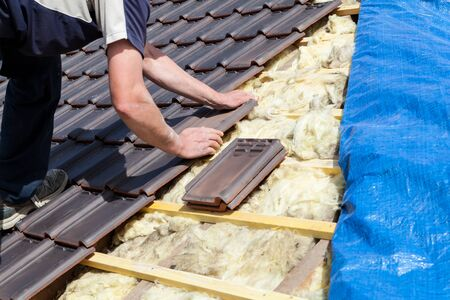 Photo for a roofer laying tile on the roof - Royalty Free Image