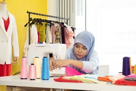 Photo pour A young Asian Muslim woman designer as a startup business owner is using sewing machine on working table in her tailor shop. - image libre de droit