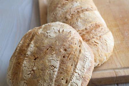 Foto für freshly baked rustic loaves of bread on wooden board - Lizenzfreies Bild