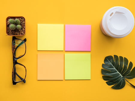 Design flat lay image of workspace desk with post-it, hot coffee, cactus, leaf and glasses on yellow background.