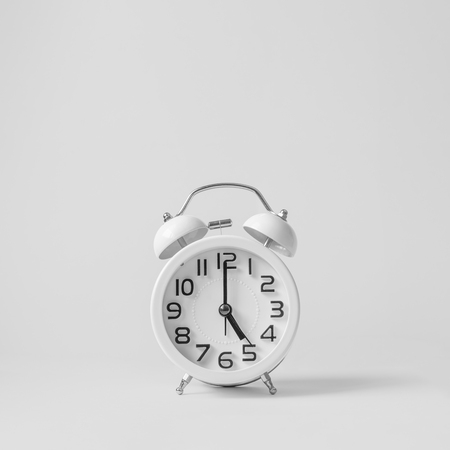 Photo pour White vintage alarm clock on white background. Concept  get off work at five. - image libre de droit
