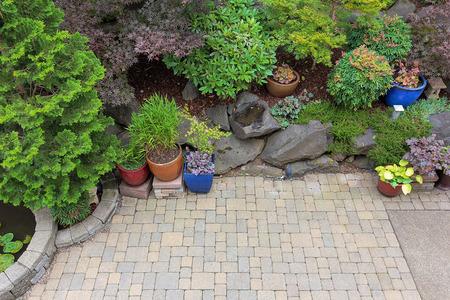 Foto de Backyard garden landscaping with paver bricks patio hardscape trees potted plants shrubs pond rocks and decor - Imagen libre de derechos