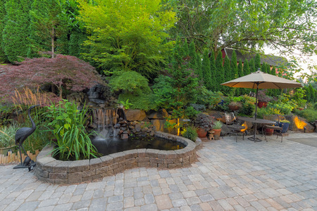 Photo for Backyard Garden landscaping with waterfall pond trees plants trellis decor furniture brick pavers patio hardscape - Royalty Free Image