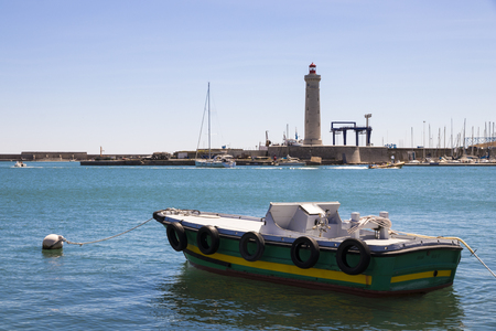 A boat with tires and a buoy with the lighthouse Phare du Mole Saint-Louis in the background. Sete, France