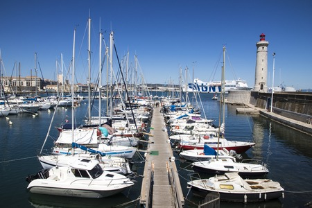 Boats in the port of Sete, Southern France, with the Phare du Mole Saint-Louis lighthouse and the GNV Majestic in the background