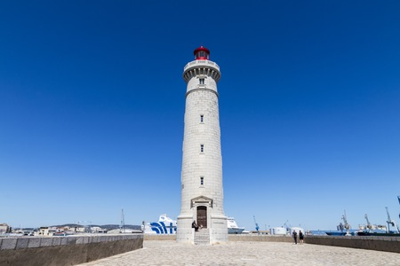 The Phare du Mole Saint-Louis lighthouse in Sete, France, with the GNV Majestic in the background and people taking pictures in the foreground