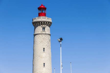 Close-up view of the Phare du Mole Saint-Louis, a white and red lighthouse in Sete, Southern France