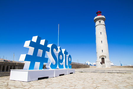 The Phare du Mole Saint-Louis, a white and red lighthouse in Sete, Southern France, with a sign with a hashtag and the name of the city in the foreground