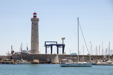 The Phare du Mole Saint-Louis, a white and red lighthouse in Sete, Southern France, with its breakwater and a ship in the foreground