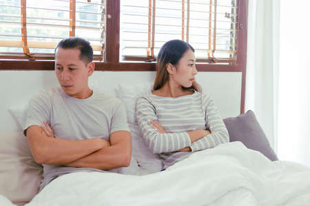 Foto de Young Asian couples are angry with each other. They turn their backs. A woman facing away from a man on the bed in the house. woman focus - Imagen libre de derechos