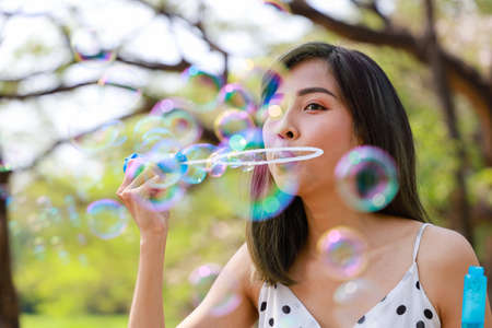 Photo for Outdoor autumn summer portrait of asian young beautiful happy woman making soap bubbles in park. Her Joyous happy in white dress. Holiday relaxation ideas - Royalty Free Image