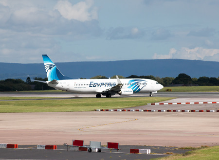 EgyptAir Boeing 737 narrow-body passenger plane SU-GEB taxiing on Manchester International Airport tarmac before departure.