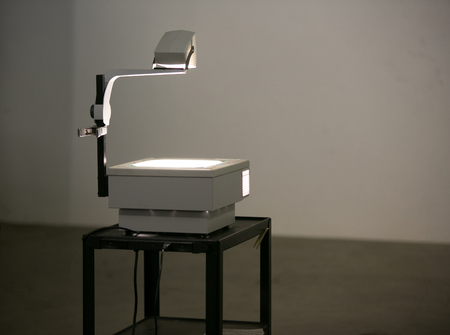 Photo for A vintage overhead projector sit on a roller cart lighting a wall ready to show overhead projection transparencies. Overhead projectors were often used in school & business before digital projection. - Royalty Free Image