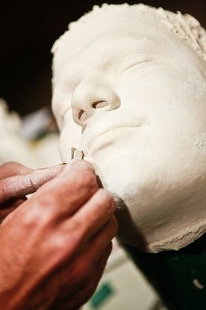 Artist working on plaster cast of a human face.