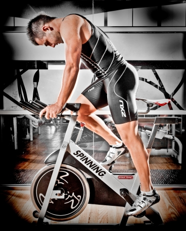 Strong fit athletic man training in a gym on a spinning bike in a health and fitness concept, sideways profile