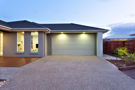 Part of this luxurious house includes a garage with a white door and illuminated by two small lights under the ceiling.