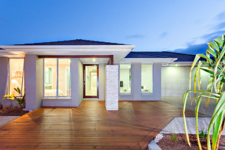 Blue sky over the luxury house and illuminated light inside and outside indicate the time of night environment. The interior lighting can be seen through the windows and it has spread to the wooden facade of the entrance. The garage has lights brighter li