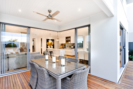 Photo pour Outdoor patio area with table set up beside an entrance to inside of a modern house with a kitchen, there are candles on the table under the fan - image libre de droit