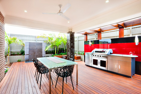 Modern and relaxing area of a luxury house, whole area covers with wooden walls, pillars and a fence, chairs are made using a beautiful carve on the wooden floor there There is a silver color gas grill cabinet near black and red wall tiles.