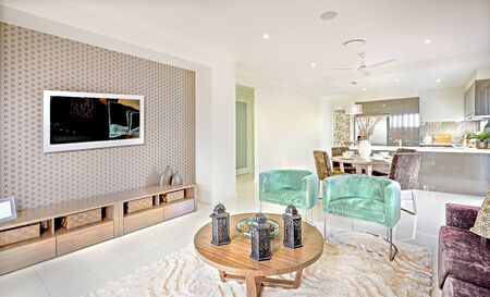 Photo for Modern house interior with living room area with a television and round wooden table with black lamps on the wool carpet beside the green chair  and dining room next to kitchen - Royalty Free Image