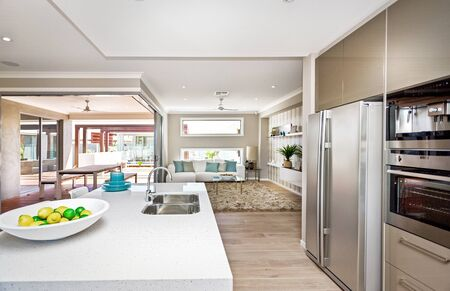 Photo pour Well-equipped kitchen area with counter-top basin, refrigerator, and other electronic equipment - image libre de droit