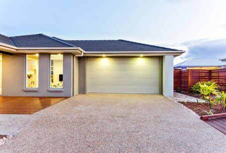Photo for Part of this luxurious house includes a garage with a white door and illuminated by two small lights under the ceiling. - Royalty Free Image