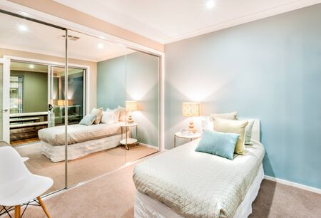 Foto de Modern and classic bedroom walls are light blue which is illminated in lights og table lamp and one wall is totally covered with big mirrors. there is a white chair behind the it and near the bed. the bad has a fat mattress with pillows on it - Imagen libre de derechos
