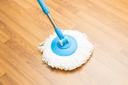 Photo pour Cleaning by use modern mop on laminated wood floor. - image libre de droit
