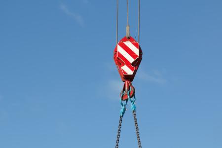 Photo pour Mobile crane hook with chains, blue sky on background - image libre de droit