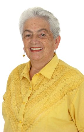 An older smiling woman in a yellow shirt over white background