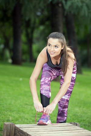 Portrait of cheerful young sportswoman tying laces before running in park