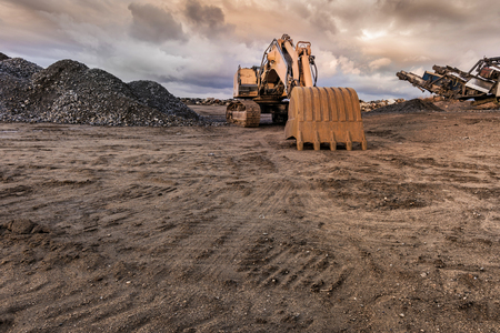 Photo pour Excavator and machine to pulverize stone in a quarry - image libre de droit