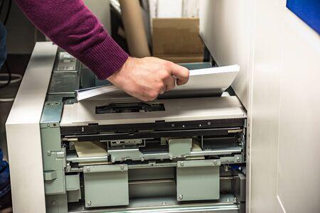 Photo pour Replenishing paper in a digital printer - image libre de droit