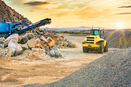 Photo pour Excavator and stone crusher in a quarry - image libre de droit